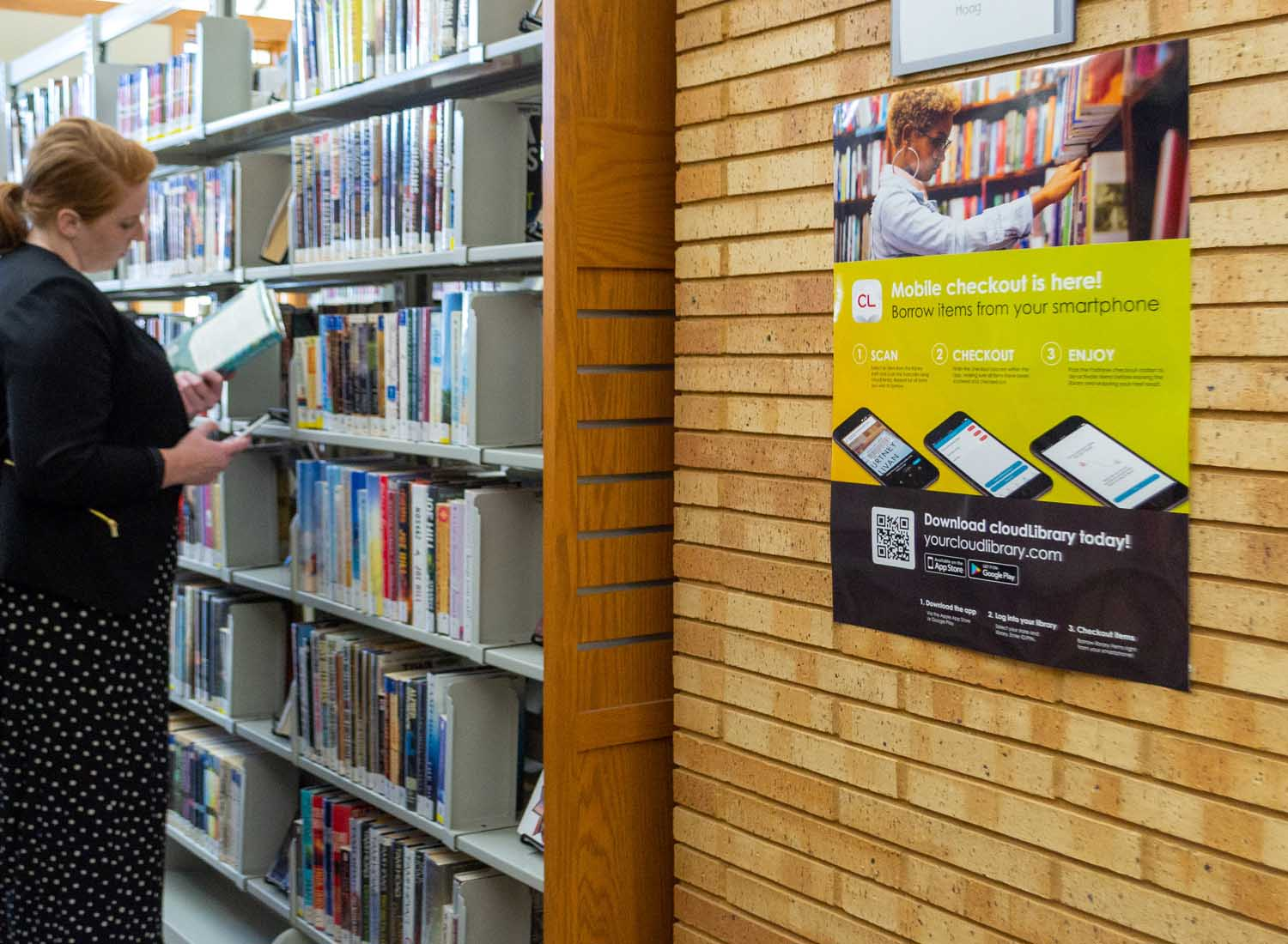 woman browsing library shelves with cloudLibrary poster
