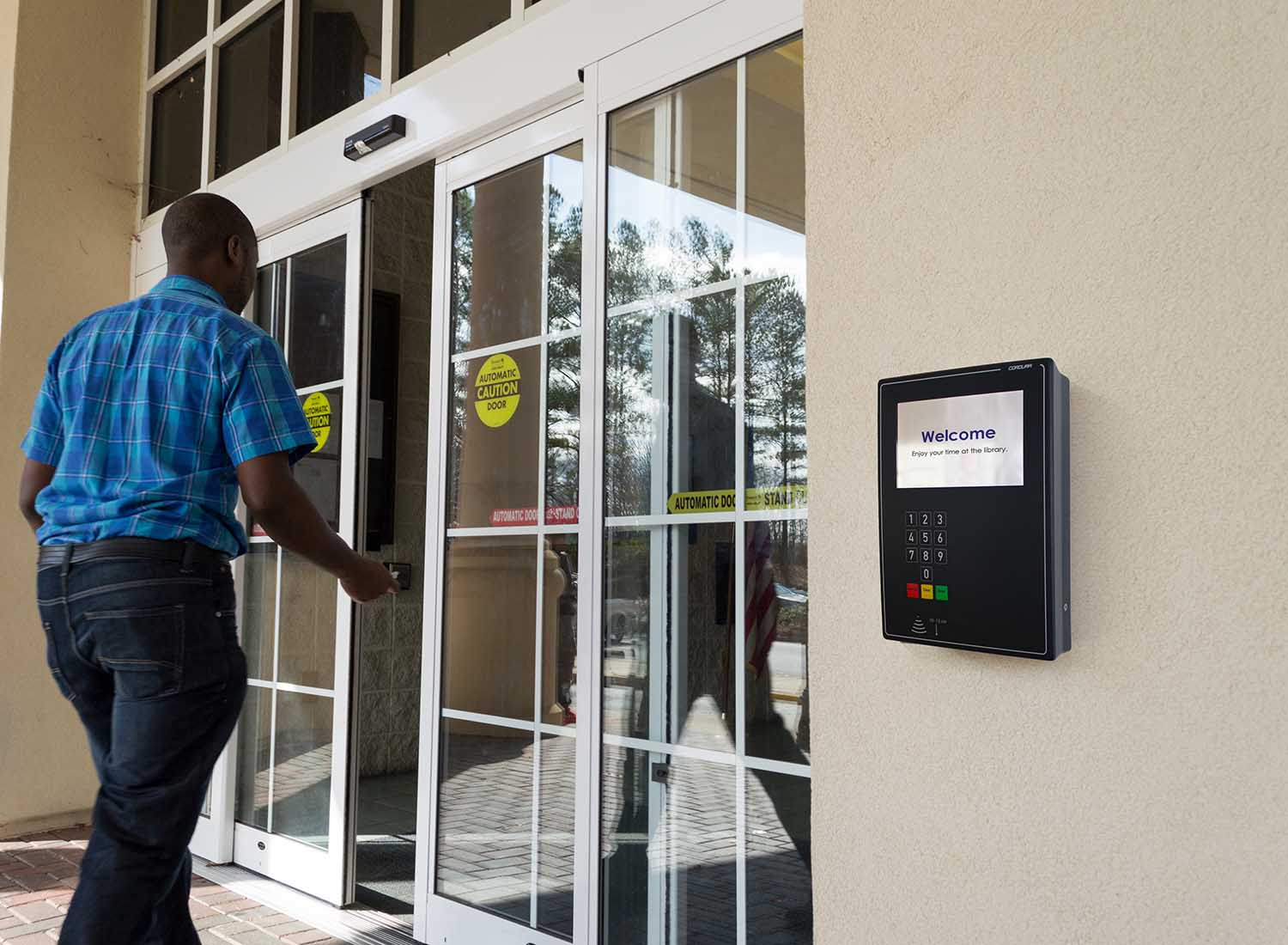 Man entering library with access control panel