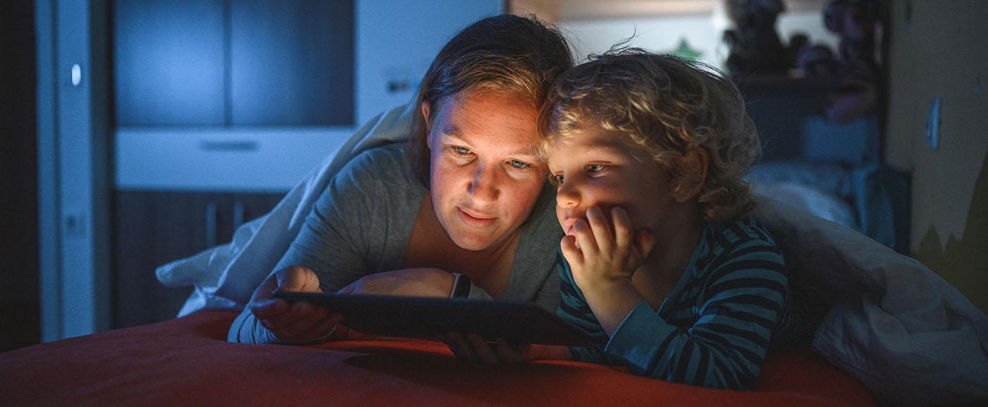 Mother child reading iPad night