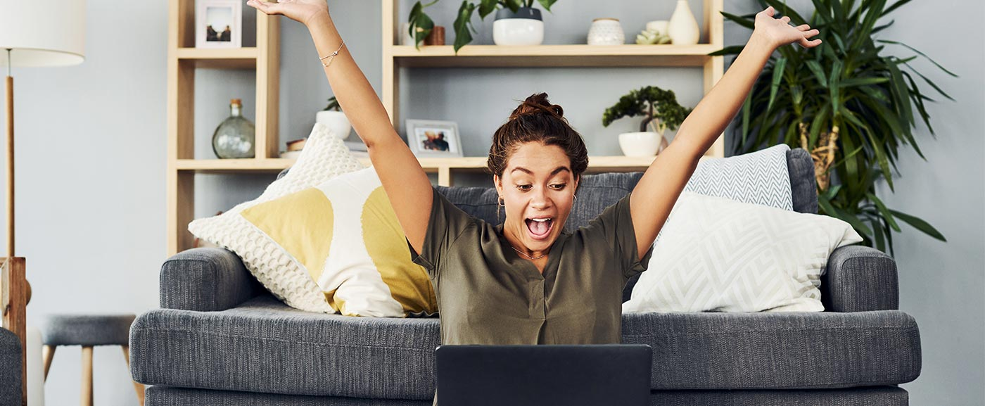 iStock-1165117030 Lady celbrating with arms up looking at laptop screen